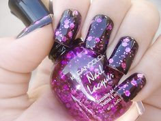 Purple glitter polish on top of a black base.