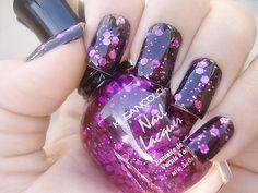 Purple glitter polish on top of a black base.