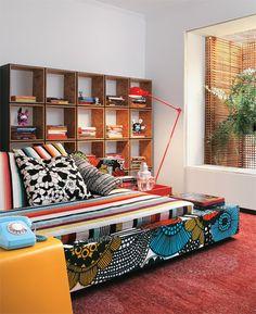 Forrado com tecidos assinados, o sofá-cama (execução da Jocal) combina com a mesinha amarela (Micasa), a luminária vermelha Lumini), a estante de módulos de OSB (Marcenaria Oliveira) e o tapete de fibra (By Kamy).