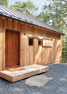 Door Design Ideas – 9 Examples Of Modern Dutch Doors | This dark wood Dutch door is the entrance to the guest house located just off the luxurious main home tucked into the forest.
