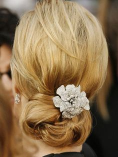 Flip hair over and spritz with hairspray all over. This will give your hair a little extra grit and keep your chignon from wilting after an hour.  Rake hair up and back with your hands, pushing it forward at the roots to encourage lift, and secure ends in a twist at the nape of your neck. Keep sticking in bobby pins and pulling out pieces to loosen the style.  Then, mist the twist with a little shine spray. This shouldn't look perfect but fast/sexy/chic.