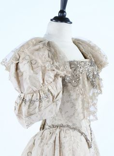 a silver and ivory brocade ball gown, circa 1895, woven with bows and foliage, the boned bodice with large sleeves, adorned with beads and sequins, Brussels lace flounce, the hem with remains of chartreuse silk trim