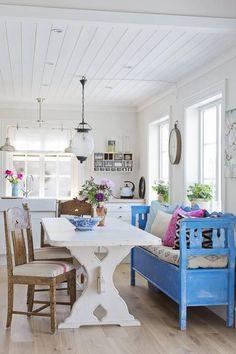 SOMMERHYTTE: Slagbenken på kjøkkenet er et vakkert blikkfang som oser av sommer, fylt med puter fra Home&Cottage og Zanz. Benken er kjøpt brukt og har fått følge av arvede stoler.Bordet er et typisk norsk bondebord som er malt hvit. Kjøkkeninnredningen er fra Ikea. Over kjøkkenet ses annen etasje nesten som en hems, med flere soverom på rad.