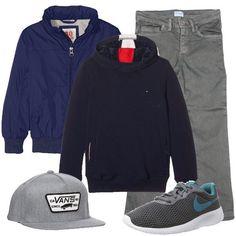 Outfit sportivo, composto da bomber blu abbinato ad una felpa con cappuccio blu scuro e ad un pantalone grigio skinny fit, sneakers grige e blu e cappello con visiera grigio.