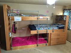Triple bunk beds with pipe ladder and drawers.