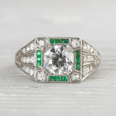 1.01 Carat Art Deco Vintage Emerald & Diamond Engagement Ring.  Center diamond is prong set inside a square setting. Accented with single cut diamonds and calibre cut emeralds. Decorated with MILLEGRAIN edges and elaborately hand engraved. Beautiful deco lines in this 1920′s find. A substantial ring with a noticeable personality but fits comfortably on the finger with a low profile. C 1920