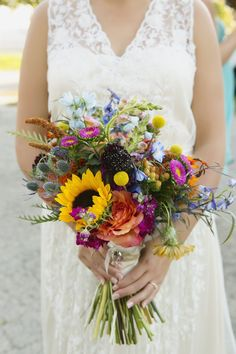This wedding bouquet is SO unique and colorful. In a rainbow of color, the bride is featured with sunflowers, roses, English thistles, greenery, and prairie flowers. We just loved how this bride opted for a colorful bouquet. It's a stunning choice for a rustic wedding. Photo by @hazeltonphoto