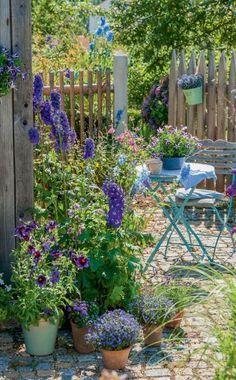 Eine ungenutzte Gartenecke wird mit Klapptisch und -stuhl ruck, zuck möbliert. Topfblumen wie Trompetenzunge 'Kew Blue', Lobelien und gestreifte Petunie leisten dem Rittersporn 'Magic Fountains' im Beet Gesellschaft