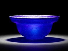 A Roman cobalt blue glass patella cup  Circa late 1st Century B.C./A.D. The carinated body with flaring rim and a pad foot, 4in (10cm) diam; 11in (4.5cm) high