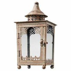 """Metal lantern decor with glass panels and a hinged door.        Product: Lantern    Construction Material: Metal and glass    Color: Distressed cream  Accommodates: (1) Candle - not included    Dimensions: 12"""" H x 6"""" W x 6"""" D"""