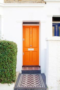 orange front door and cool tiles add high impact curb appeal.  home decor and interior decorating ideas.
