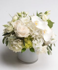 Sublime Whites A sublime collection of brilliantly white blooms including hydrangea, roses, orchids, and lisianthus are arranged in a white glass vase for this simple yet stunning design.