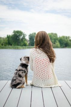 My friend Toni and her 6-month-old Miniature Australian Shepherd sitting on a dock by the lake. Pet photography. Man's best friend. Dog photography.