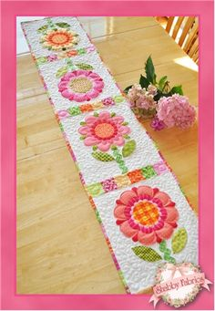 """Fun Flowers Table Runner Kit: Add some color to your table with this fun and adorable 12 1/2"""" x 58 1/2"""" runner! The flowers and leaves are cut out from a pre-printed panel making this a quick and easy fusible applique project. Simple pieced sashing and pieced binding is added for extra charm! This project goes together in just a few hours making it ideal to work on with your children or grandchildren.."""