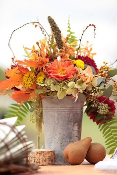 Rustic Fall Arrangement in tall pail; fruit at base connects flowers to table providing balance.