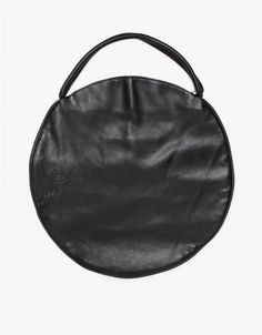 From Jasmin Shoran, a large sized leather circle bag with top handles and Brass zip closure. Features small front interior pocket with magnetic closure, and large interior pocket with natural canvas lining.   	•	Oversized circular leather bag  	•	Top c