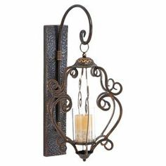 "Wall-mounted metal candle lantern with a scrolling silhouette.  Product: Candle lanternConstruction Material: MetalColor: BrownAccommodates: (1) Candle - not includedDimensions: 25"" H x 13"" W x 12"" D"