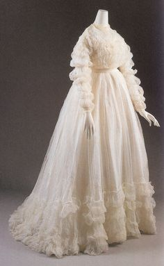 Dress, 1864, bleached tartalan muslin with matching sash. Collection: The Museum of the City of New York