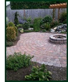 Pavers and easy care landscaping make for a unique back yard setting with firepit at center by Evergreen Landscaping & Ponds