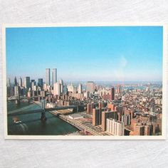 Vintage postcard of lower Manhattan with the Twin Towers of the World Trade Center in the distance. 1980s.  On the lower left is the East