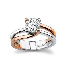 Modern in design this split shank two-tone solitaire engagement ring evolves around the center stone. The prongs for the round diamond center rise out of the shank two are rose gold and two are white gold swooping up and crossing on the sides for a touch of elegance.  Also available in yellow gold 18k and Platinum