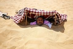 A patient buried in the hot sand looks out from under a shade that protects his face from the sun