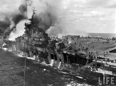 """Crew aboard the stricken aircraft carrier USS Franklin (""Big Ben"") battle huge blaze after the ship was hit by two bombs resulting in 724 killed, 265 wounded, Pacific March 1945. She stayed afloat and was later repaired."""