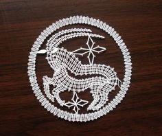 Znamení zvěrokruhu - kozoroh Kozoroh je paličkovaná krajka z bílé kordonetky vhodná k zarámování nebo do pasparty. Průměr znamení cca 13 cm.