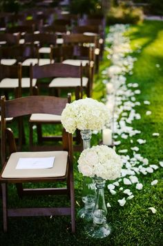 pretty outdoor aisle with white flower petals and raised flower stands at the end of the aisle. dark wood folding chairs nicely set off the white flowers.