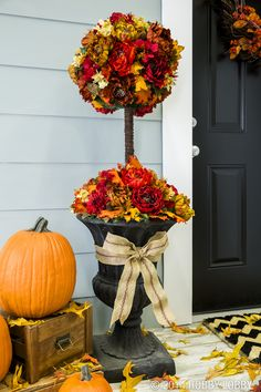 """To create this fall topiary: Place 12"""" half Styrofoam ball in large vase. Spray paint dowel rod brown then place through center of Styrofoam half ball. Play 10"""" Styrofoam ball on rod at desired height. Once form is complete, hot glue moss all over topiary to cover any Styrofoam. We used leaves from greenery garland and placed them throughout to give it a more realistic look. Wrap wooden dowel with brown grape vine cording. Once above steps have been completed, attach fall flowers and fall colored leaves with hot glue, balancing colors throughout."""