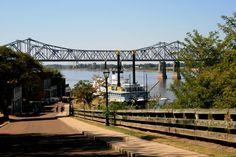 Scene of Mississippi River bridge and Natchez Under The Hill.