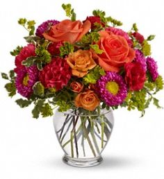 How Sweet It Is  Light orange roses, orange spray roses, hot pink carnations and matsumoto asters, red miniature carnations and more are delivered in a lovely glass vase.