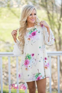 You'll be wishing your toes were in the sand, watching the sunset in this beautiful floral dress. Features a ivory bodice with vibrant floral colors, lace sleeves, and criss-cross open back. Has lining for extra coverage. Dress it up with your favorite wedges or wear it casually with a pair of sandals.