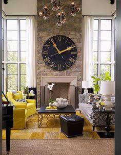 Black and yellow living room features a two story ceiling lined with a glass globe modular chandelier illuminating a two story stone fireplace lined with a French clock flanked by tall windows dressed in black banded curtains.