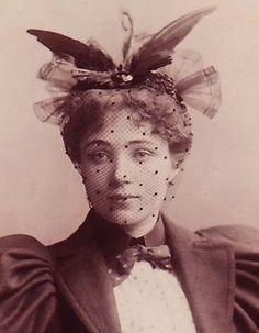 Hat, possibly from 1890s. Black dotted netting and feather wings perch on top.