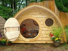 Hobbit Hole Playhouse with round front door and windows, cedar roof, cedar clapboard siding, all natural wood construction @Janessa Penner |   See More about hobbit hole, playhouses and front doors.