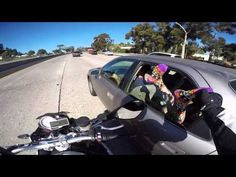 Motorcyclist grabs some feet hanging out a car window on the freeway.