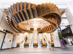 Utilizing the original 1931 wooden escalator tracks & now weighing over 5 tonnes, a major new work called 'Interloop' 2017 twists and hovers, over the heads of commuters. Installed in Sydney's Wynard train station, more than 50 meters of the  heritage timber-stepped escalators built for the  station in 1931 by @otiselevatorco . By Sydney artist Chris Fox @foxprojects who designed and engineered the structure.  by Josh Raymond.