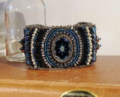 Bead Embroidered Cuff Bracelet Blue Intaglio by ThePeacockShop on Etsy https://www.etsy.com/listing/156850643/bead-embroidered-cuff-bracelet-blue