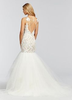 Inspired by the Haley Paige Kalea. Ivory lace fit to flare bridal gown, elongated bodice with nude lining and scalloped V-neckline, low open back with strap detail, tiered tulle skirt. Because this dr