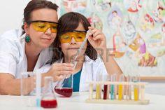 química: Muchacho joven en la clase de ciencias de primaria haciendo experimento…