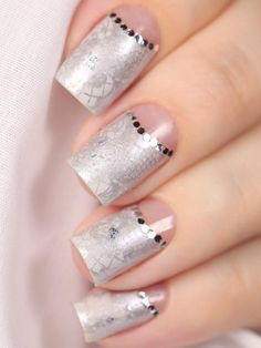 To achieve this gorgeous design, you may want to put a base of a lighter silver nail polish up to the curve for the half moon. Then pick up a stenciled design that you want and then place them over the nails and paint with a darker silver. Then use some silver rhinestones for more accent.
