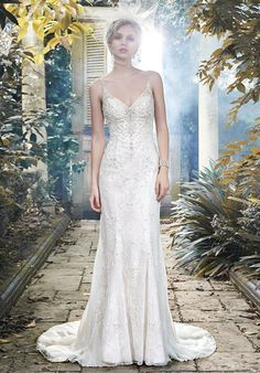 Glamorous Swarovski crystals, shimmering pearls and sparkling sequins drift down the tulle and lace skirt of this sheath wedding dress, accented with V-neckline and dainty, pearl encrusted spaghetti straps. Finished with plunging scoop back and pearl buttons over zipper closure.