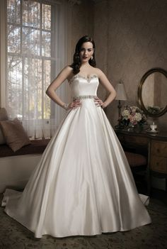 Classic gown for a classic bride! Satin Justin alexander gown features an embellished bust line and matching sash.