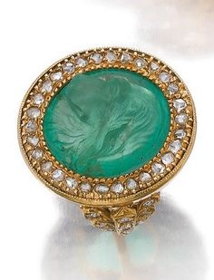 An antique gem set and diamond ring, late 19th Century. Set at the centre with an emerald carved with the profile of a hunting dog, the frame and shoulders set with rose diamonds. #antique #ring