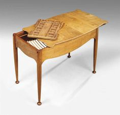 PEDER MOOS (1906-1991) SEWING TABLE, CIRCA 1950 probably unique, carved walnut, mahogany and beechwood, the sliding top with ebony inlay, opening to reveal carved tray and storage basket 22 in. (56 cm.) high; 24½ (61.5 cm.) wide; 13¾ (35 cm.) deep