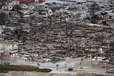 People (bottom) walk near the remains of burned homes after Hurricane Sandy in the Breezy Point neighborhood of the Queens borough of New York City. Over 50 homes were reportedly destroyed in a fire during the storm. Breezy Point, Aerial Images, Hurricane Sandy, Before I Die, Adventure Is Out There, Places To See, City Photo, Things To Do, Bucket