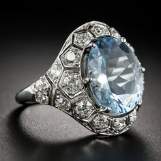 A refreshing splash of cool blue sparkles from the center of this unusual, impressive and thoroughly stunning aquamarine ring, hand fabricated in platinum - circa 1920s-30s. The glistening 4.55 carat gemstone is embraced all around with 1.35 carats of bright-white European-cut diamonds glittering from within mostly individual honeycomb style settings. This guaranteed smile maker measures a sizable 13/16 inch from top to bottom with about the same width.