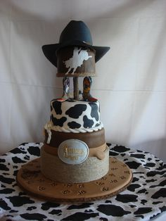 "- Grooms cake to reflect grooms love of rodeo...with handmade gumpaste ""Justin Roper"" cowboy hat as a topper.  Mini ""brands"" in base represent bride and grooms initials.  Bodacious belt buckle molded from actual buckle owned by the groom.  The hand cut rodeo bull silhouette in honor of the grooms bull riding achievements."