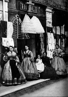 Photo of hoop skirts hanging outside a storefront, undated.   From Retronaut.